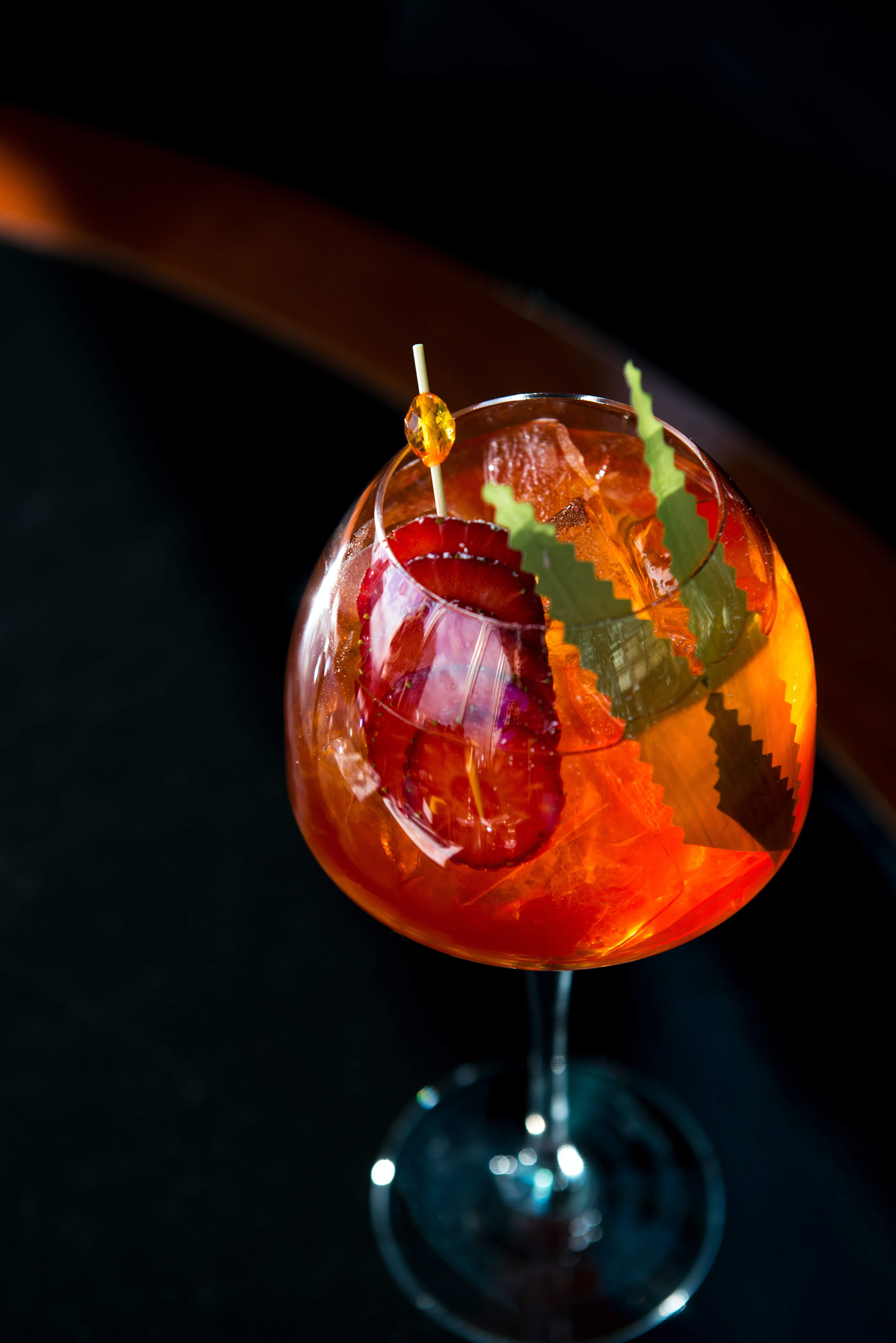 Deep orange coloured cocktail in glass with black background