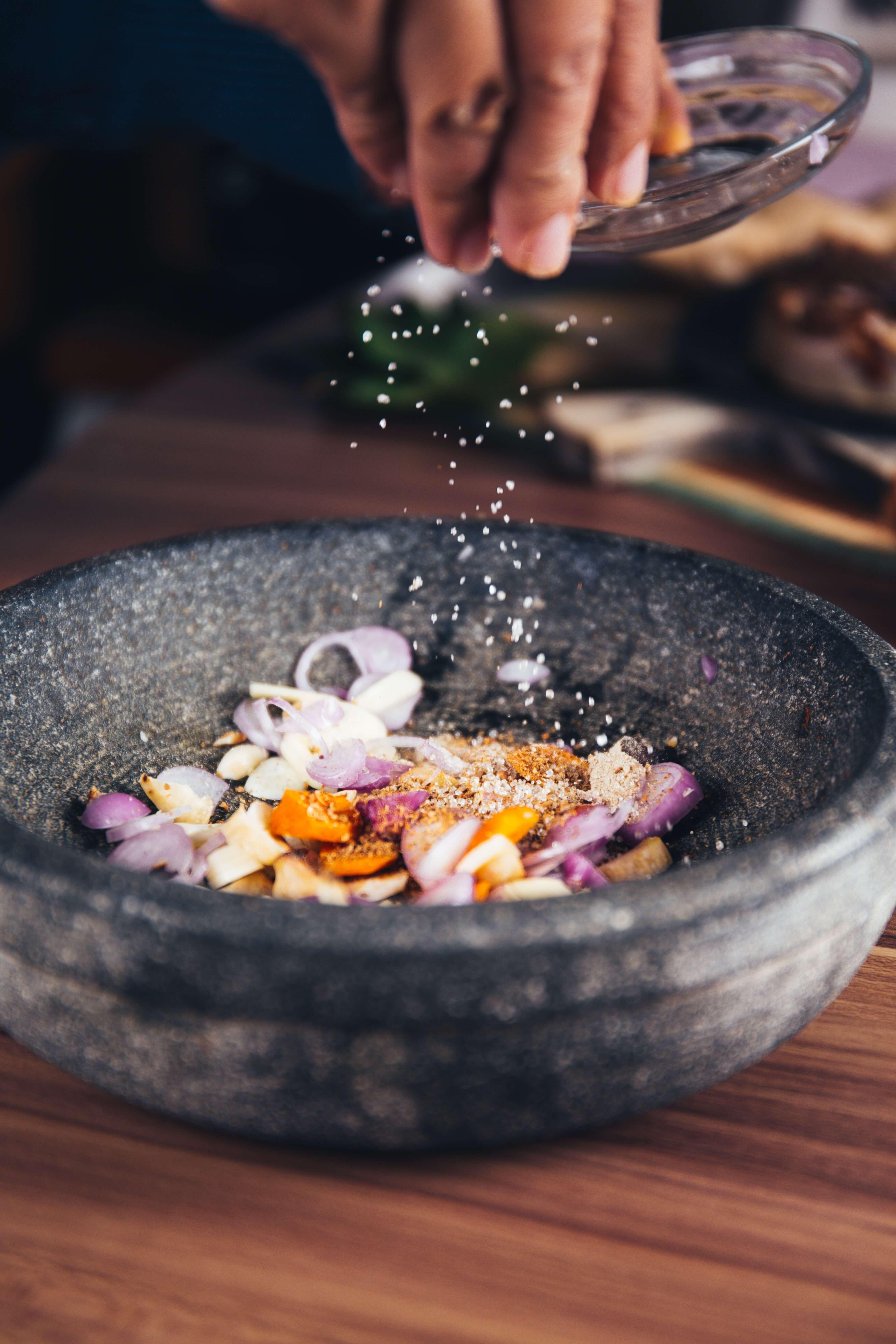 Food in dish being seasoned